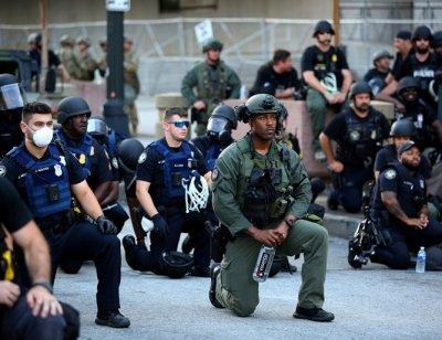 Полицаи и протестиращи заедно коленичат в памет на убития Флойд